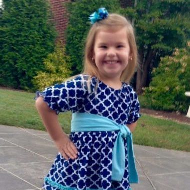 Smiling girl with blue and white dress with teal belt and bow.