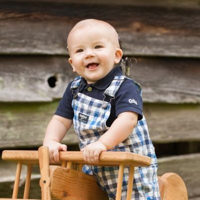 Toddler boy posing on wooden airplane in front of a side of a barn.
