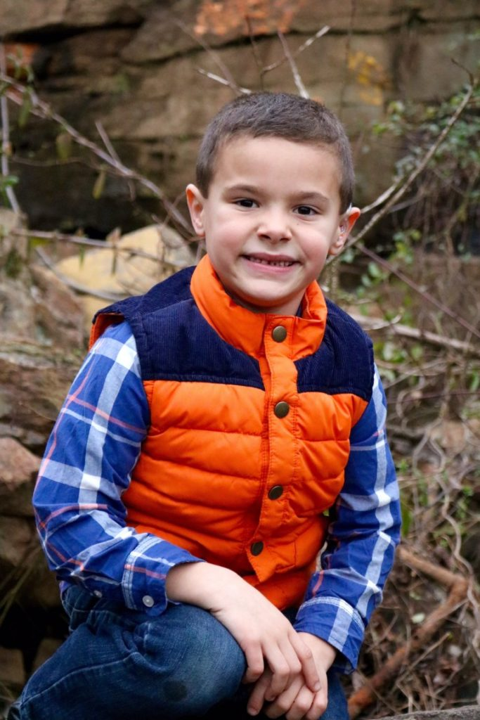 Young boy sitting in nature, wearing blue plaid shirt and orange vest.