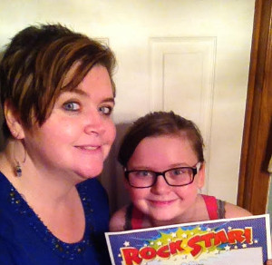 """Mom and daughter smiling at the camera, holding a certificate that says """"rock star."""""""