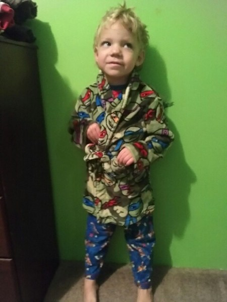 Young boy wearing green and blue PJs, leaning against a green wall.