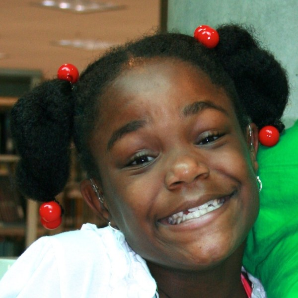 Smiling girl with pigtails.