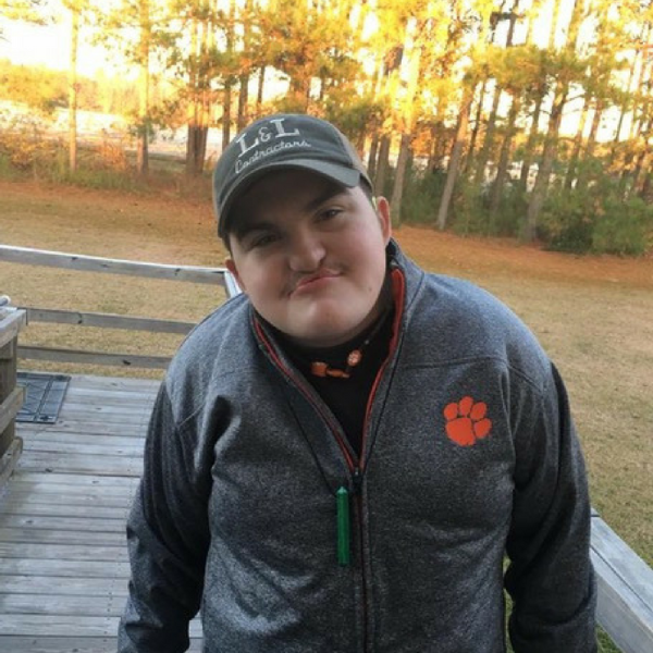 Young man smiling into the camera, wearing a baseball cap and a Clemson jacket.
