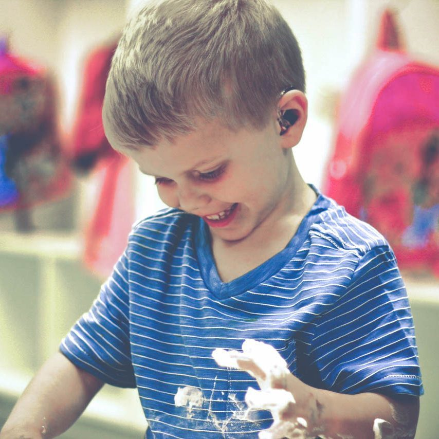 Young, blond boy with hearing aids playing with soap suds.