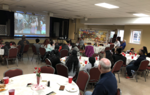 Many families are gathered and watching a video about Camp Sertoma in SC.
