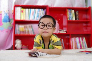 Young boy with big, oval black-rimmed glasses is reading a book in his pink and red room.