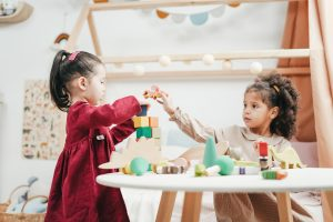 Two girls plays with building blocks
