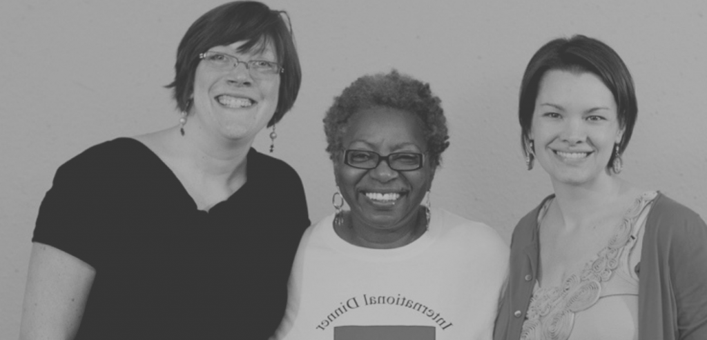 Photograph of three women with their arms around each other, smiling at the camera